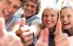 Happy guys and girls expressing happiness by showing thumbs while smiling